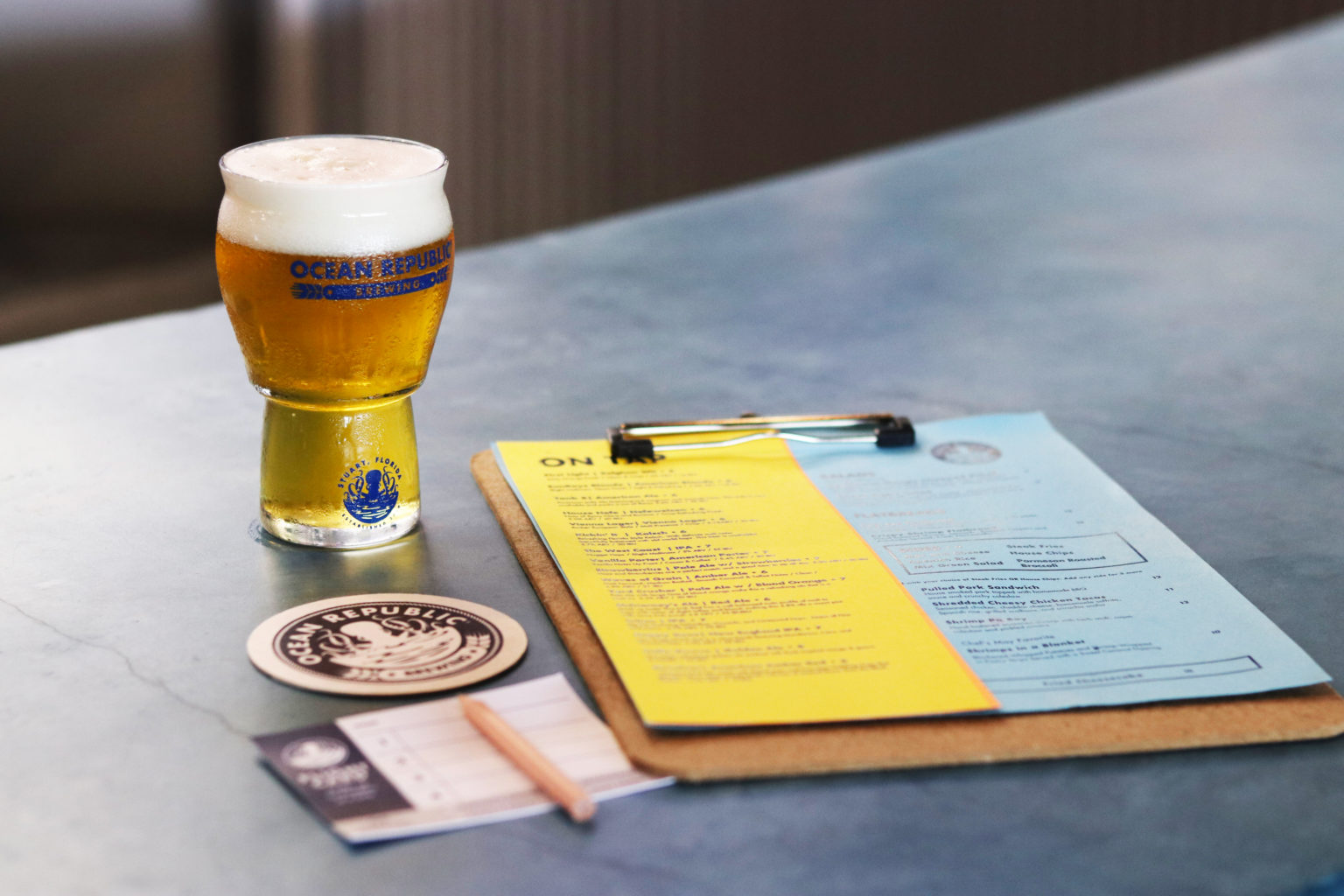 Ocean Republic Brewing Collateral on Bar with Beer