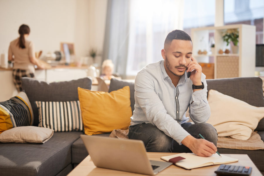 Portrait of modern man speaking by phone while working from home in cozy interior, copy space
